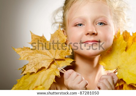 Little cute girl with autumn leaves
