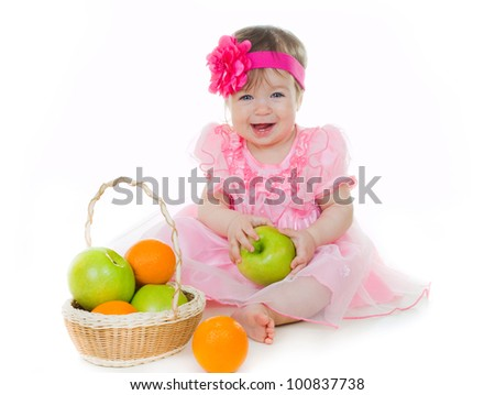 Little cute girl with basket of green apples and oranges on white background. - stock photo