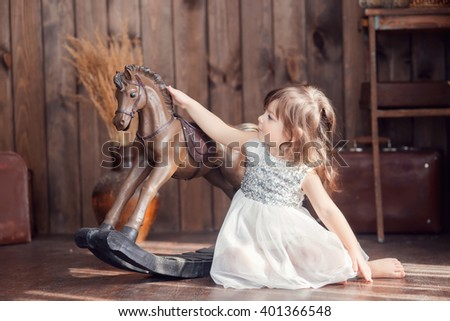 little cute girl with brown hair in a white dress sitting on the floor and petting a horse rocker, a look to the side, tenderness - stock photo