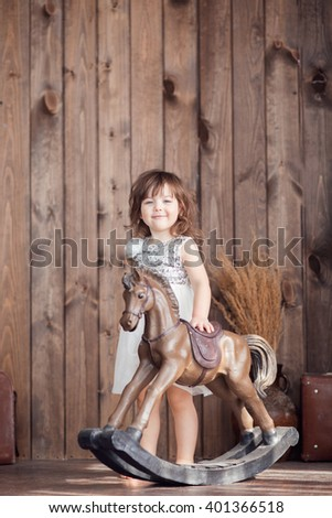 little cute girl with brown hair in a white dress standing on the floor and petting a horse rocker, a look to the side, tenderness - stock photo