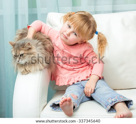 little cute girl with cat on white sofa