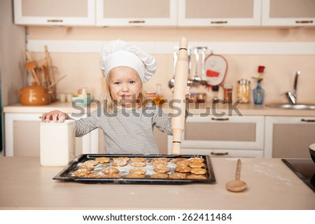 Little cute girl with chef hat and rolling pin looking at camera and preparing cookies. Kitchen interior. Concept for young kitchen hands - stock photo