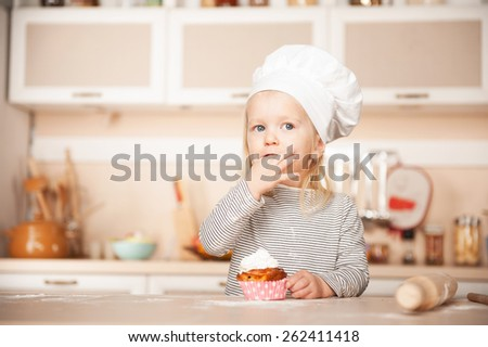 Little cute girl with chef hat tasting cake. Kitchen interior. Concept for young kitchen hands - stock photo