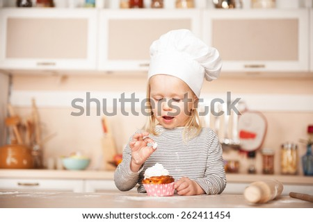 Little cute girl with chef hat tasting cake. Kitchen interior. Concept for young kitchen hands