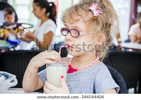 Little cute girl with glasses is drinking lemonade at pastry shop in summertime. - stock photo