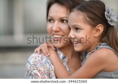 Little cute girl with happy mother on a walk