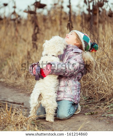 little cute girl with her dog breed White Terrier walking in a field - stock photo