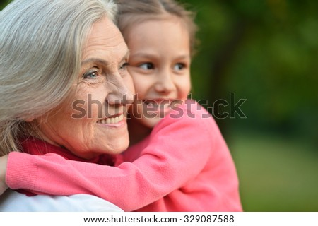 Little cute girl with her grandmother in summer park - stock photo