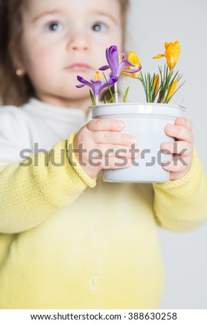 Little cute girl with holding a pot with flowers on the white background