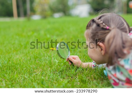 Little cute girl with magnifying glass looking at flower. - stock photo