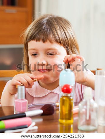 Little cute girl  with  mom's lipstick