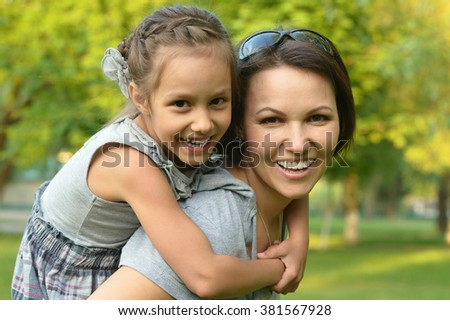 Little cute girl with mother in park - stock photo