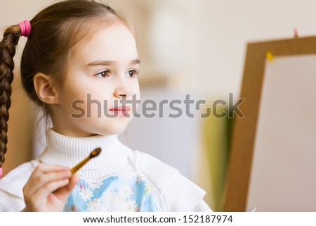 Little cute girl with paint brush and easel