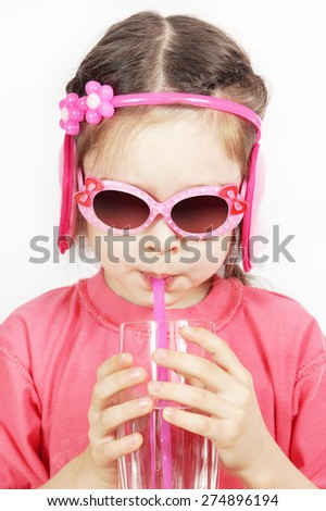 Little cute girl with pink sunglasses drinking water with a pipe - stock photo