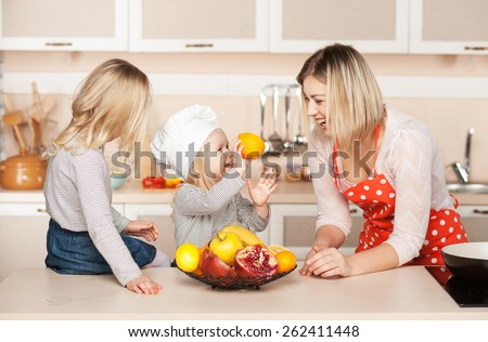 Little cute girl with sister smiling and showing orange to their mother while helping to cook salad. Kitchen interior. Concept for young kitchen hands - stock photo