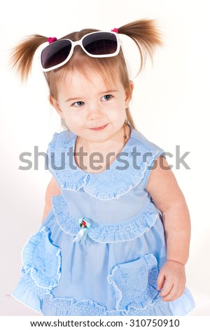 Little cute girl with sunglasses in a blue dress, studio portrait on white background