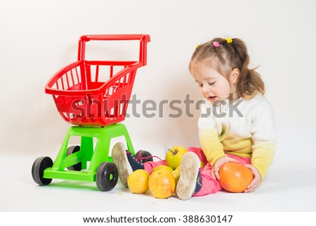 Little cute girl with supermarket cart and fruits on the white background