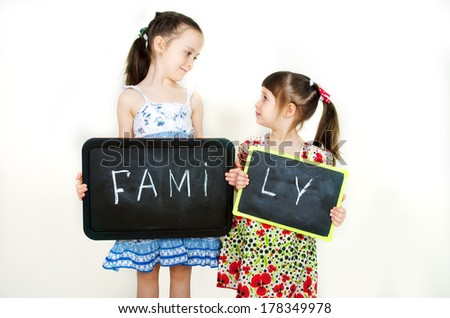 Little cute girls hold a board with the word Family - stock photo