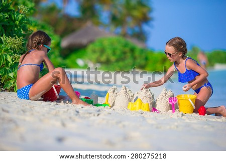 Little cute girls playing with beach toys during tropical vacation - stock photo