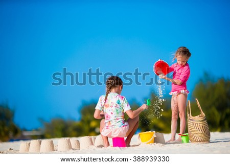 Little cute girls playing with beach toys during tropical vacation