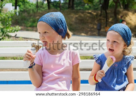 Little cute girls (sisters) eat ice cream, selective focus. - stock photo