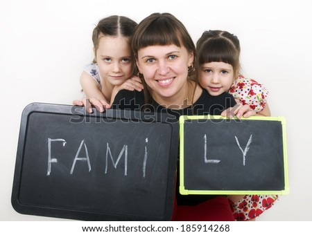 Little cute girls with mom hold a board with the word Family - stock photo