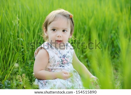 Little cute happy baby girl first walking in summer green grass park