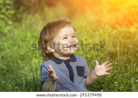 Little cute happy smiling baby boy sitting in field on fresh green grass sunny day, horizontal picture - stock photo