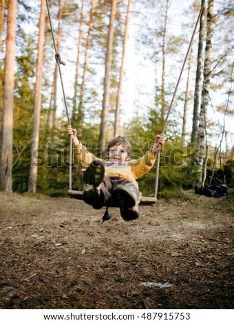 little cute happy smiling boy swinging in autumn wood, lifestyle people concept