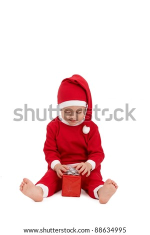 Little cute kid sitting in santa costume with present box.?