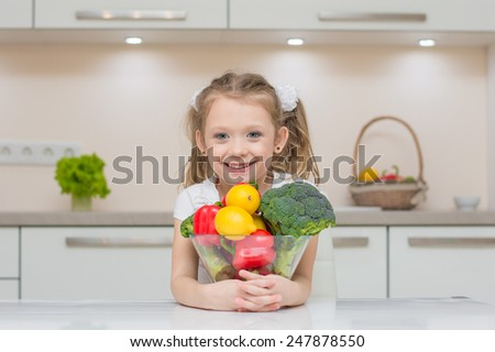 Little cute preschool girl in the kitchen smiles and hugs bowl full of healthy fresh vegetables - broccoli, paprika, lemons - stock photo