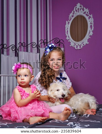 Little cute puppy and sister at home - stock photo