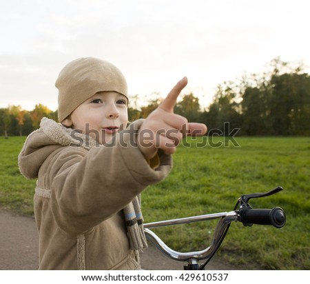 little cute real boy on bicycle emotional smiling close up outside in green amusement park
