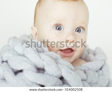 little cute red head baby in scarf all over him close up isolated, adorable - stock photo