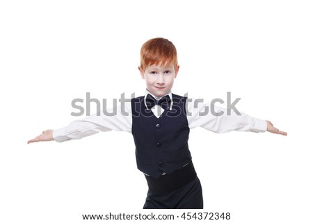 Little cute redhead boy in vest with bow tie pose with spread hands. Portrait of well-dressed child in bow tie shows inviting gesture, isolated on white background - stock photo