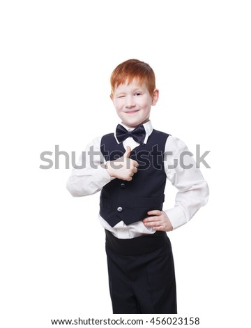 Little cute redhead boy in vest with bow tie shows thumb up and wink. Portrait of well-dressed child in bow tie, approval,, satisfaction gesture. Kid isolated on white background - stock photo