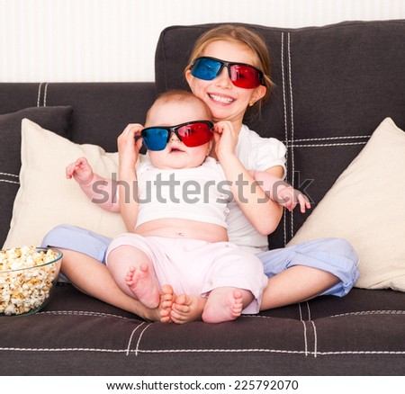 little cute  sisters watching 3d TV - stock photo