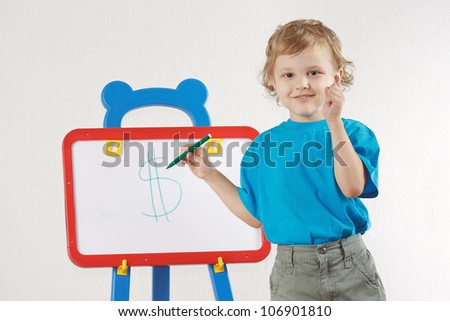 Little cute smiling boy drew a dollar sign on the whiteboard - stock photo