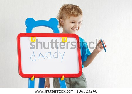 Little cute smiling boy wrote the word daddy on whiteboard - stock photo