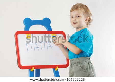 Little cute smiling boy wrote the word papa on whiteboard - stock photo