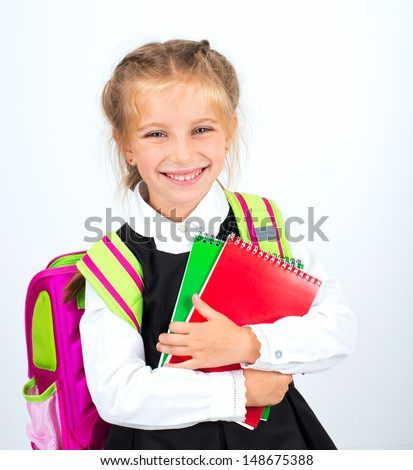 little cute smiling girl with a stationery on a white background - stock photo