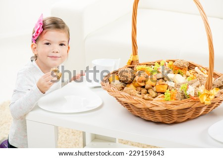Little cute smiling girl with hair-clip, holding a delicious pastry that is taken out of a wicker basket full of pastry.