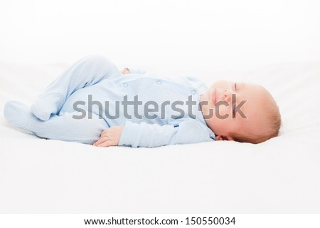 Little cute smiling newborn baby child sleeping bed white isolated - stock photo