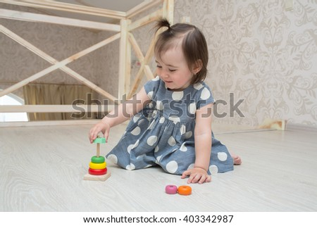 little cute toddler girl  indoors playing wooden toys