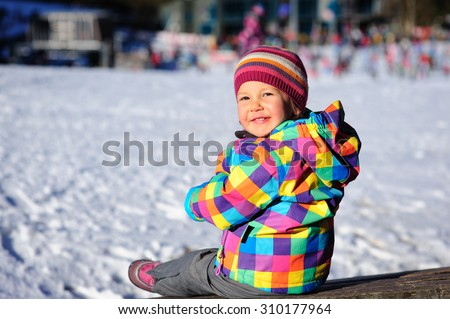 Little cute toddler girl wearing a bright colorful winter jacket and a knitted hat with snow in the background - stock photo