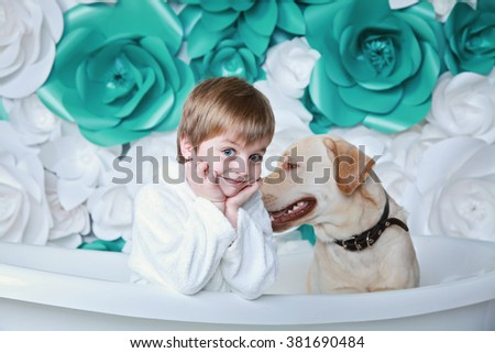 little cute 4-years boy in bathrobe with his dog labrador retriever sit in the bath and smile with white and turquoise flowers on the background