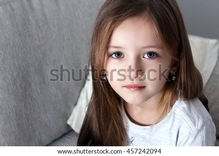 Little cutie. Cheerful little girl holding arms crossed and looking at camera with smile while standing against grey background