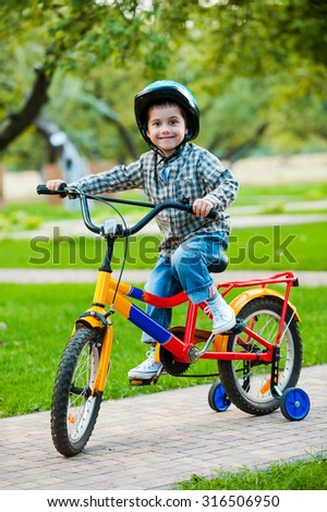 Little cyclist. Cheerful little boy looking at camera and smiling while riding on bicycle - stock photo