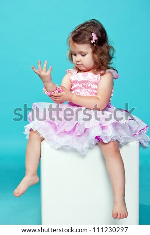 Little, dark-haired baby girl getting ready for the celebration and dressing up in jewelry. Baby dressed in a pink fluffy dress. Isolated on blue background.