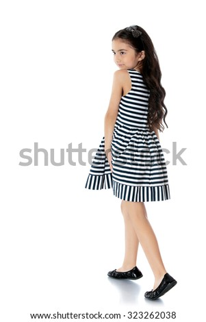 Little dark-haired girl in beautiful summer dress in stripes stands sideways to the camera-Isolated on white background - stock photo